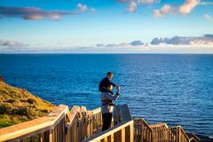 Father giving his son piggyback ride. At Hallett Cove boardwalk while enjoying sunset, South Australia Royalty Free Stock Image