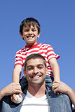 Father giving his son piggyback ride outdoors. Attractive father giving his son piggyback ride outdoors Stock Photography