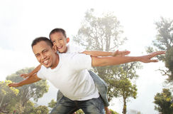 Father giving his son piggyback ride outdoors Royalty Free Stock Image