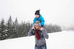 Father giving his son piggyback. Winter nature. Young father outside giving his son piggyback. Having fun with his son, playing in the snow. Foggy white winter Stock Images
