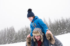 Father giving his son piggyback. Winter nature. Young father outside giving his son piggyback. Having fun with his son, playing in the snow. Foggy white winter Royalty Free Stock Images