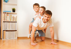 Father giving his two sons piggy back ride Royalty Free Stock Photos