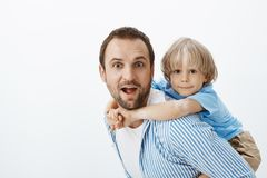 Father giving piggyback ride to cute blond son with vitiligo. Potrait of carefree beautiful dad and kid, hugging. Showing tongue and making funny faces while stock photos