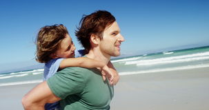Father giving piggyback to his son at beach stock footage