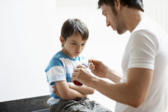 Father Giving Son Cough Syrup. At home Royalty Free Stock Image