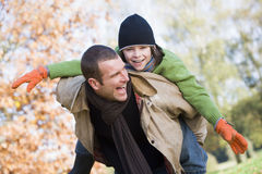 Father giving son piggyback. Through autumn woods Royalty Free Stock Images