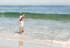Father giving son a piggyback on the beach Stock Images