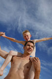 Father giving son piggyback ride. Young dad carrying his son on his shoulders, view from below Stock Photography