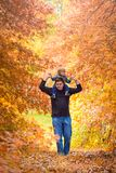 Father giving son piggyback ride. In the autumn park, South Australia Royalty Free Stock Photo