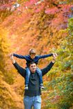 Father giving son piggyback ride. In the autumn park in South Australia Stock Photos