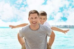 Father giving son piggyback ride. On pier Royalty Free Stock Images