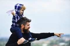 Father giving son ride on back in park. Father and son building together a paper airplane. Happy child playing with toy. Paper plane against summer sky royalty free stock images