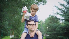 Father giving son ride on back in park. Portrait of happy father giving son ride on his shoulders and looking up. Cute stock footage