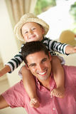 Father Giving Son Ride On Shoulders Indoors. Smiling Royalty Free Stock Photography