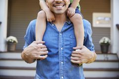 Father Giving Son Ride On Shoulders Outside House stock photos
