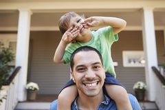 Father Giving Son Ride On Shoulders Outside House stock images