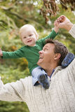 Father giving young son ride on shoulders. Outside Royalty Free Stock Photos