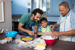 Father and grandfather looking at boy breaking egg in bowl. While preparing food in kitchen at home Stock Photography