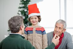 Father And Grandfather Looking At Son During. Happy father and grandfather looking at son wearing Santa hat during Christmas at home Royalty Free Stock Photos