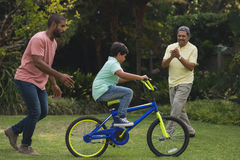 Father and grandfather motivating boy while riding bicycle. At park Stock Image