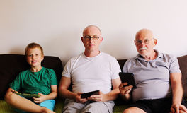 Father, grandfather and son. Playing games on tablets and reading ebook Royalty Free Stock Photos