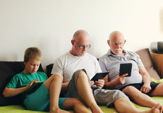 Father, grandfather and son. Playing games on tablets and reading ebook Stock Photos