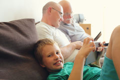 Father, grandfather and son. Playing games on tablets and reading ebook Royalty Free Stock Image