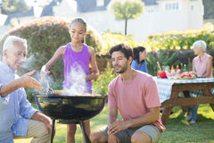 Father and grandfather watching while girl preparing barbecue Royalty Free Stock Photo
