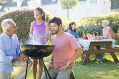 Father and grandfather watching while girl preparing barbecue Stock Photo