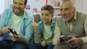 Father and grandpa playing video game at home, boy cheering for victory, relax
