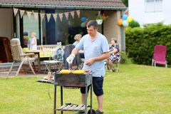 Father grilling meat in the garden for lunch Stock Photo