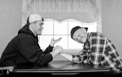 Father and grown son armwrestling by an inside window. Horizontal black and white image of a caucasian father and grown son having an arm wrestling challenge Royalty Free Stock Photos