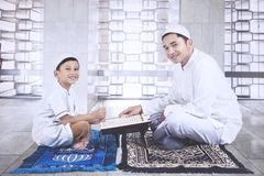 Father guides his son to reading the Quran Stock Images