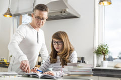 Father guiding daughter in doing homework at table Stock Images