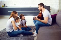 A father with a guitar sings a song for his family. A happy family stock images