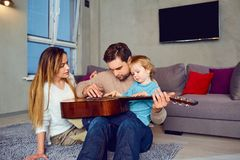 A father with a guitar sings a song for his family. A happy family stock photo