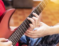 Father hands his son to play red guitar. stock image
