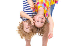 Father hands holding his smiling children upside down. Father hands holding his smiling and playful children upside down on white background Royalty Free Stock Photography