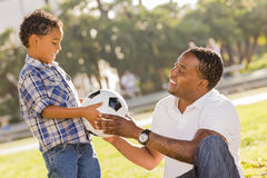 Father Hands New Soccer Ball to Mixed Race Son. African American Father Hands New Soccer Ball to Mixed Race Son at the Park stock photography