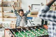 Foosball. Father and happy son playing kicker in modern office Stock Image