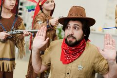 father in hat and bandana and little sons in indigenous costumes with toys playing together stock photos