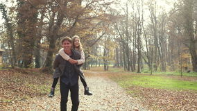 Father having fun with daughter, carrying her on his back at park stock video footage