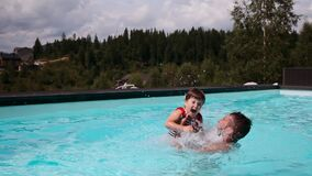 Father playing with daughter in swimming pool