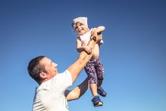Father small daughter fun as family lifestyle portrait in front of blue sky stock photos