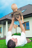 Father having fun with a son. Father having fun with a baby in yard Royalty Free Stock Images