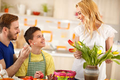 Father having fun with son while mother arranges tulips in vase. Father having fun with son while mother arranges colorful tulips in vase Stock Photos