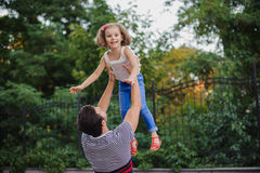 Father having fun and throwing up his daughter in park Stock Images