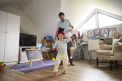 Father Having Game Of Tag With Children In Playroom Stock Photography