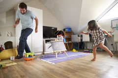 Father Having Game Of Tag With Children In Playroom Royalty Free Stock Photo
