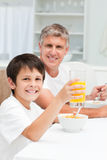 Father having his breakfast with his son Stock Photos